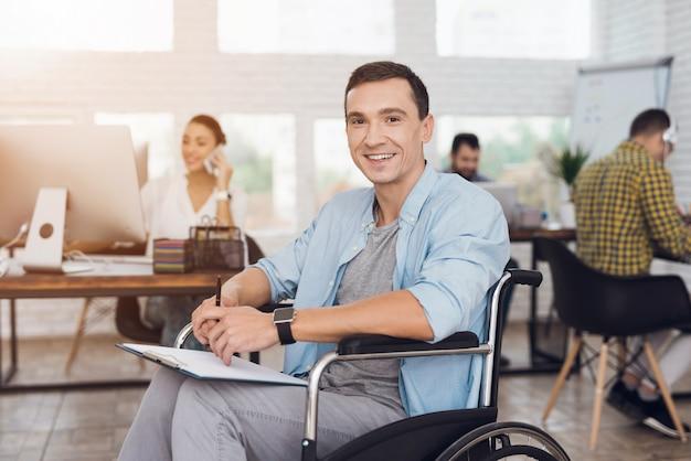 Homem deficiente na cadeira de rodas com a tabuleta no escritório. Foto Premium