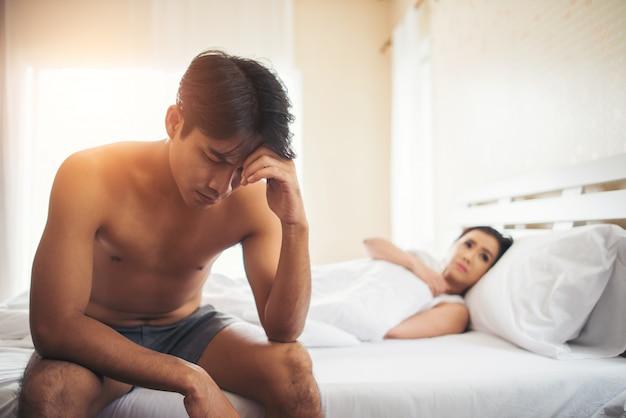 Homem deprimido sentado na cama no quarto tem problema com sua esposa Foto gratuita