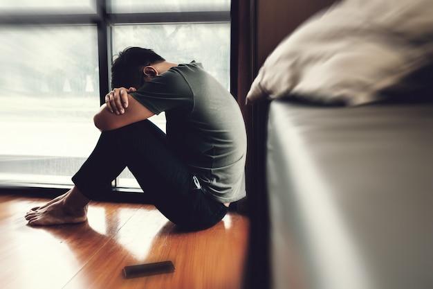 Homem deprimido. triste homem infeliz sentado no chão e segurando sua testa enquanto estiver com dor de cabeça Foto Premium