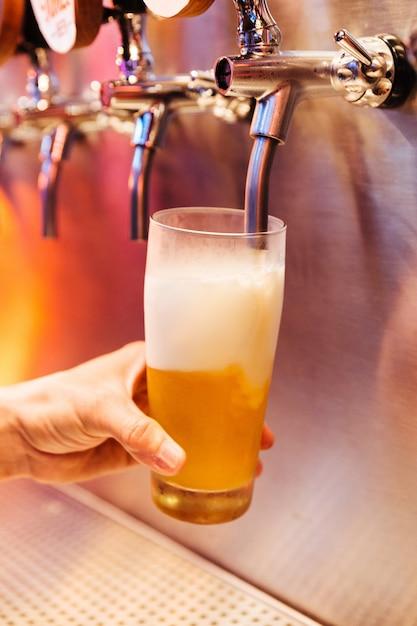 Homem derramando cerveja artesanal de torneiras de cerveja em vidro congelado com espuma. Foto Premium