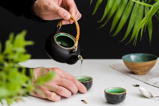 Homem derramando chá na xícara de chá Foto gratuita