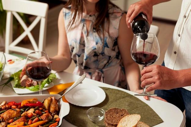 Homem derramando vinho em vidro na mesa de jantar Foto Premium
