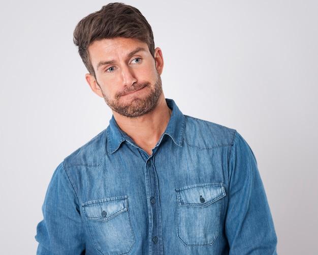 Homem desapontado vestindo uma camisa jeans Foto gratuita