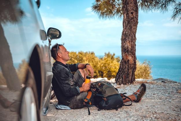 Homem descansando depois de caminhar de carro Foto Premium