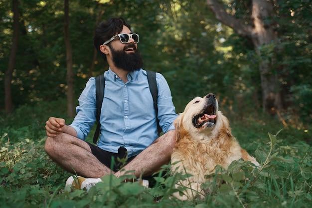 Homem descansando na grama sentado cruzou as pernas com seu cachorro Foto gratuita