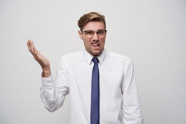 Homem descontente vestindo uma camisa branca e gravata azul, com óculos brancos. Foto gratuita