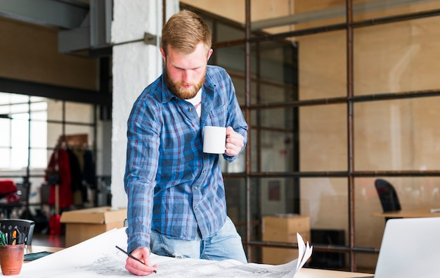 Homem, desenho, impressão azul, com, xícara café segurando, em, seu, escritório Foto gratuita
