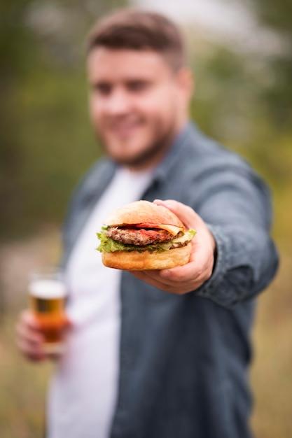 Homem desfocado com tiro médio segurando hambúrguer Foto gratuita