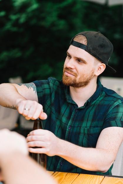 Homem, desgastar, boné, abertura, a, garrafa cerveja Foto gratuita