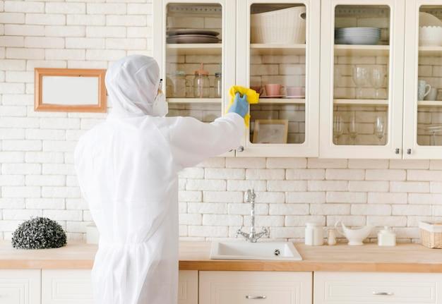 Homem desinfecção de cozinha em traje de proteção Foto Premium