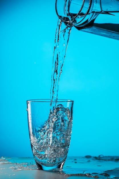 Homem despeja água de um copo em um copo sobre fundo azul em estúdio Foto Premium