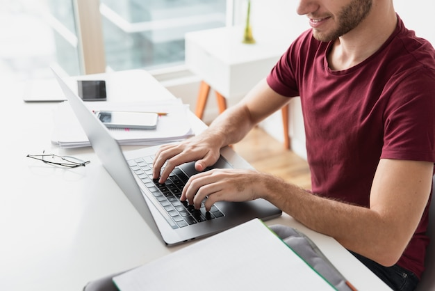 Homem digitando em seu teclado vista alta Foto gratuita