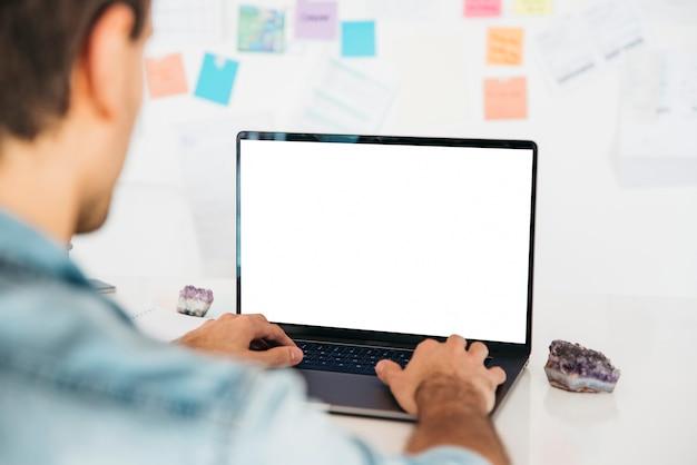 Homem digitando no laptop na mesa perto da parede com notas Foto gratuita