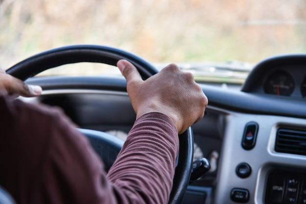 Homem, dirigindo, car / motorista mãos, ligado, volante, dirigindo meu carro, estrada Foto Premium