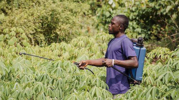 Homem do campo desinfetando o campo Foto gratuita