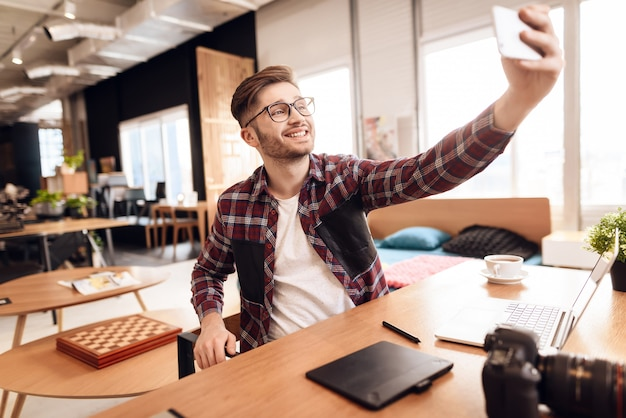 Homem do freelancer que toma o selfie no portátil que senta-se na mesa. Foto Premium
