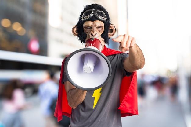 Homem do macaco do super-herói que grita por megafone em fundo não focado Foto Premium