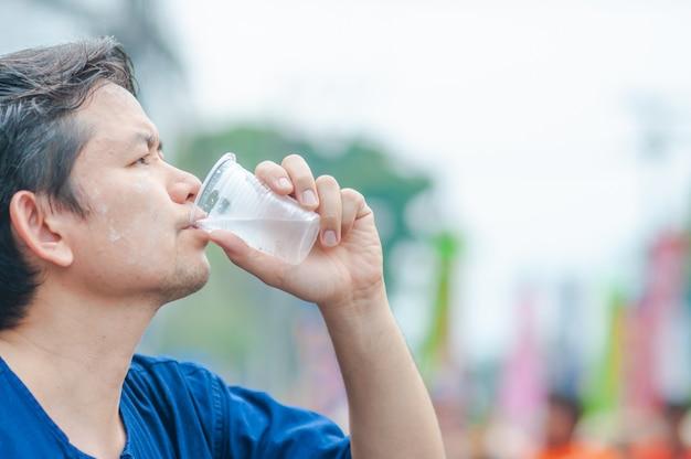 Homem do norte da tailândia beber água fria em vidro plástico durante a atividade de participação ao ar livre Foto gratuita