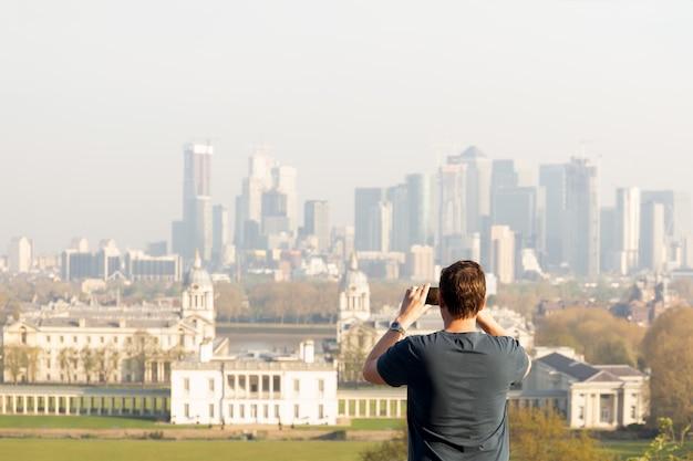 Homem do turismo que toma a foto da opinião da cidade com telefone celular ao viajar no verão. Foto Premium