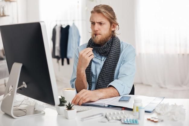 Homem doente barbudo doente senta-se na frente do computador, tenta se concentrar no trabalho, mantém os óculos na mão. trabalhador de escritório exausto cansado, tem estilo de vida sedentário, isolado contra o fundo do escritório. Foto gratuita