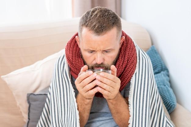 Homem doente, com febre, bebendo chá quente de cura Foto Premium