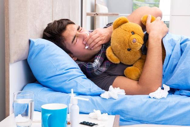 Homem doente com gripe, deitada na cama Foto Premium