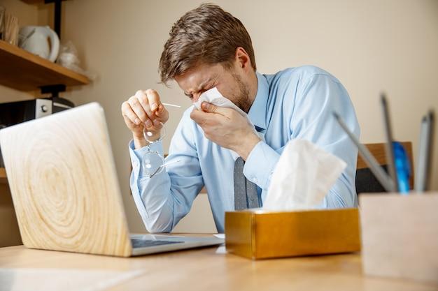 Homem doente com lenço, espirros, assoar o nariz enquanto trabalhava no escritório, empresário pegou resfriado, gripe sazonal. Foto gratuita