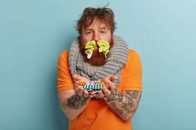 Homem doente com roupas quentes, lenços de papel no nariz e termômetro Foto gratuita