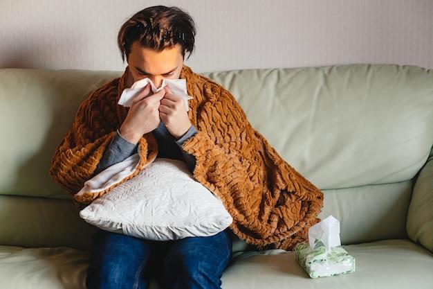 Homem doente segura tecido ao redor do nariz Foto Premium