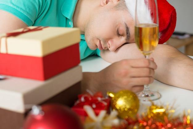 Homem dormindo na mesa com presentes de natal e taça de champanhe Foto gratuita
