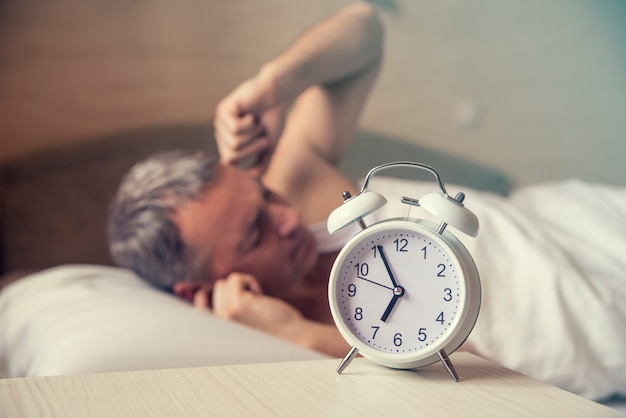 Homem dormindo perturbado pelo despertador no início da manhã. homem irritado na cama acordado por um barulho. acordado. homem deitado na cama desligando um despertador pela manhã às 7h Foto gratuita