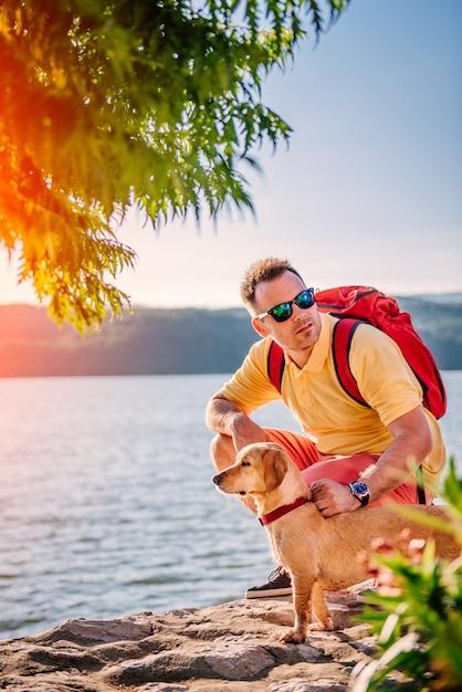 Homem e cachorro agachado na doca de pedra à beira-mar Foto Premium