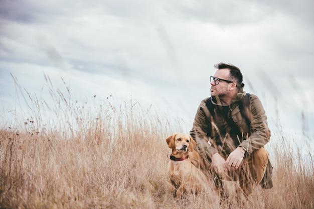 Homem e cachorro na grama alta Foto Premium