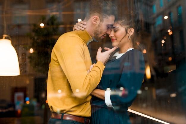 Homem, e, charming, mulher abraçando, em, restaurante, perto, janela Foto gratuita