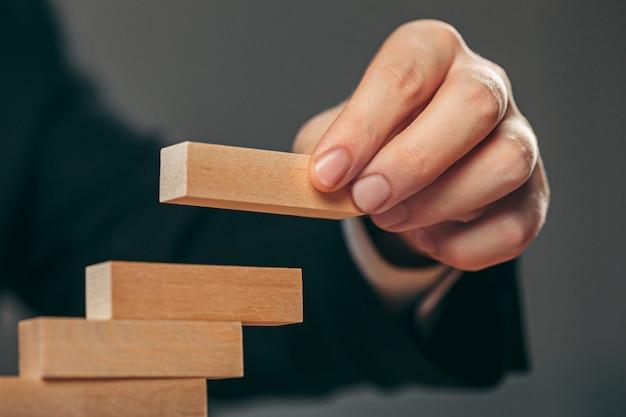 Homem e cubos de madeira na mesa. conceito de gestão Foto gratuita