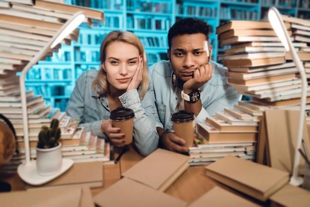 Homem e menina branca que sentam-se na tabela cercada por livros. Foto Premium