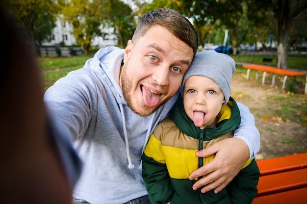 Homem e menino tirando uma selfie com as línguas Foto gratuita