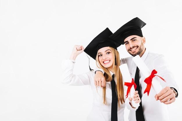 Homem e mulher alegre com diplomas Foto gratuita