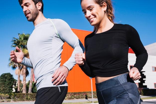 Homem e mulher alegre correndo juntos Foto gratuita