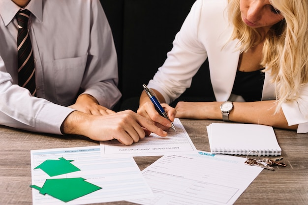 Homem e mulher assinando documentos de empréstimo Foto gratuita
