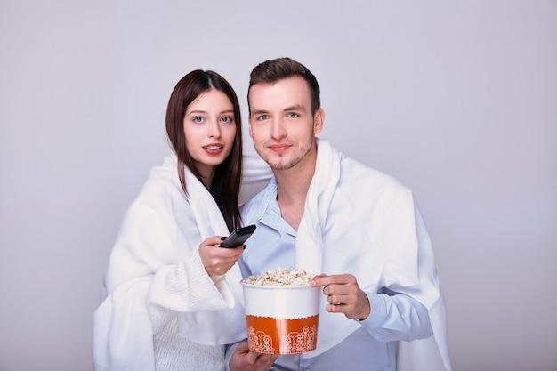 Homem e mulher assistindo tv e comendo lanche de pipoca. Foto Premium