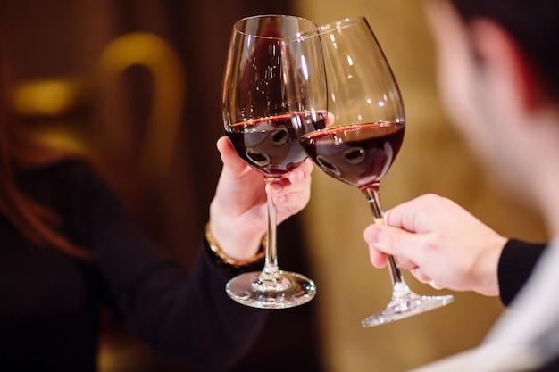 Homem e mulher bebendo vinho tinto. na foto, close-up mãos com óculos. Foto Premium