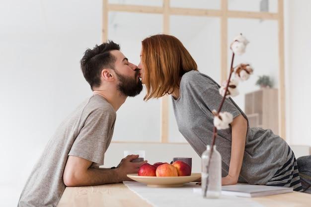 Homem e mulher beijando na cozinha Foto gratuita