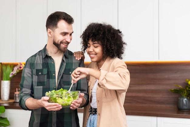 Homem e mulher bonita tentando saborosa salada Foto gratuita