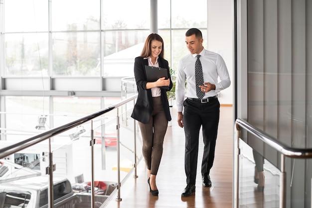 Homem e mulher caminhando juntos na concessionária Foto gratuita