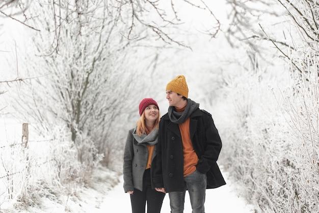 Homem e mulher caminhando na floresta de inverno Foto gratuita