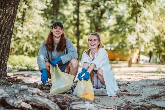 Homem e mulher catando lixo do parque. eles coletando a maca no saco de lixo Foto gratuita