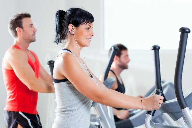 Homem e mulher com elíptica cross trainer no ginásio Foto Premium