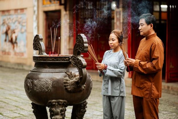 Homem e mulher com incenso no templo Foto gratuita