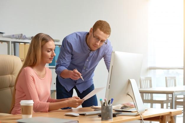 Homem e mulher coworking no documento de negócios, gerando idéias Foto gratuita